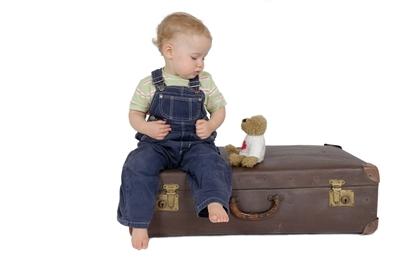 Junge auf Koffer Babynest